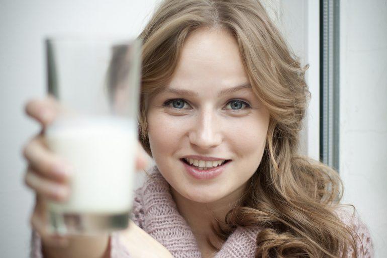 Mujer sonriendo con un vaso de leche