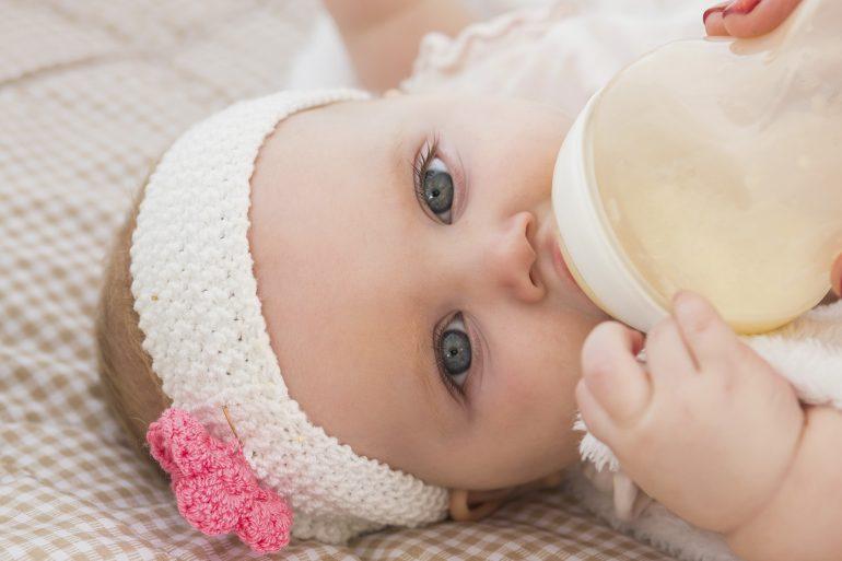 Bebé con biberón de leche